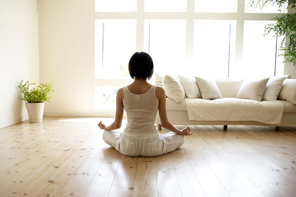 Young woman performing yoga pose in living room