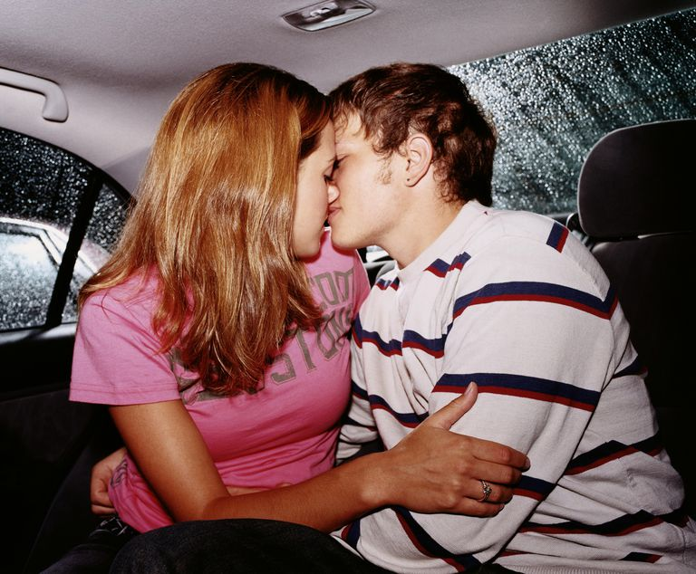 Young couple kissing in back seat of car, side view
