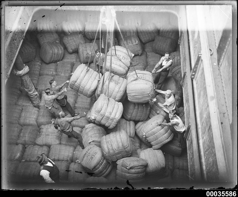 Cargo hold in MAGDALENE VINNEN with crew men positioning wool bales, March 1933