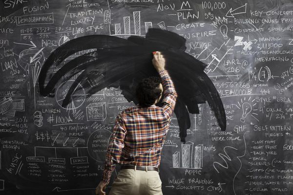 Young male erasing business plans on blackboard
