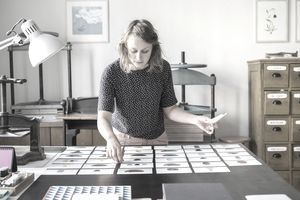 Female designer checking photos of ceramics