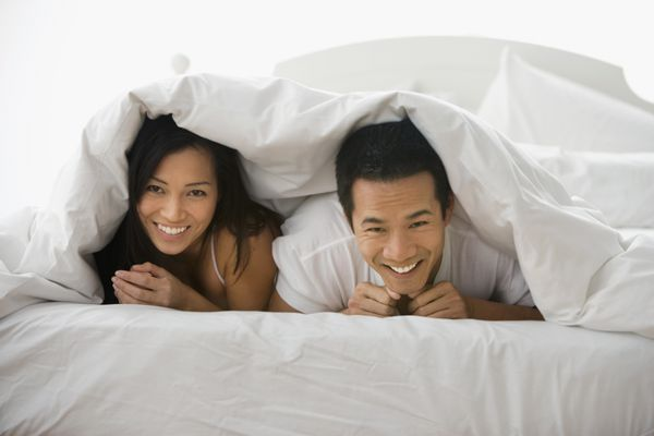Asian couple laying under blanket