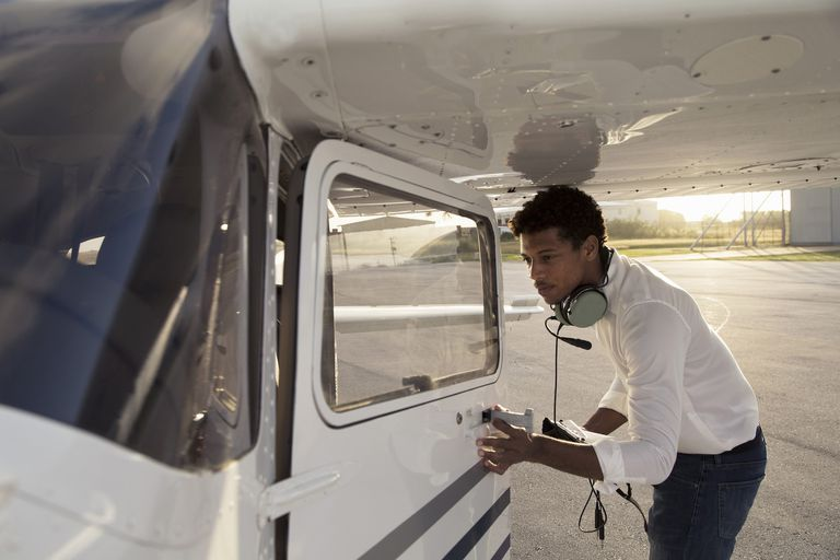 Young pilot getting in plane.
