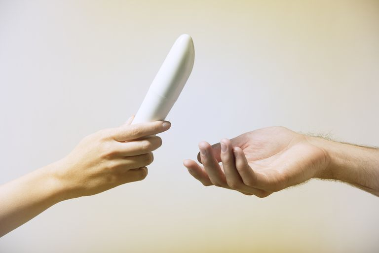 A hand reaches out to another hand holding a vibrator.
