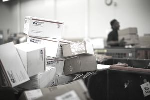 USPS mail sorting facility and stack of packages
