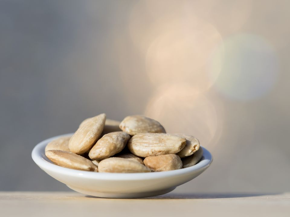 Closeup of a plate of fried peeled almonds on a wooden table illuminated by sunlight