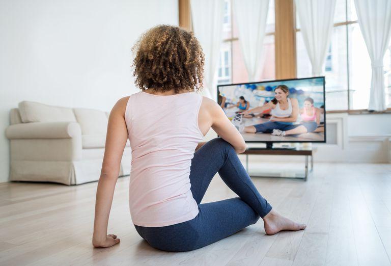 woman watching Pilates workout DVD