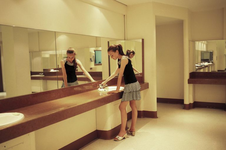 Girl (12-14) standing at hand basin, turning tap