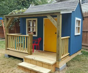 A playhouse with a front porch, windows, and door.