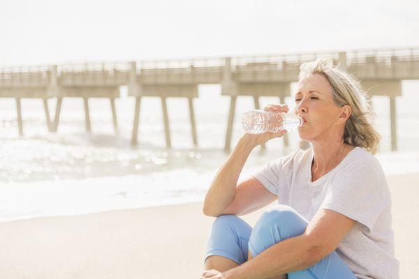 USA, Florida, Jupiter, Senior woman drinking water on beach