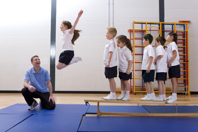 7 year old child development - kids in school gym, girl jumping
