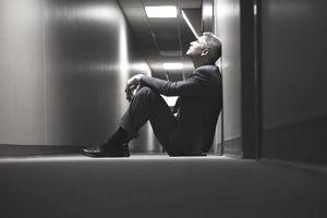 Caucasian businessman sitting on floor in corridor