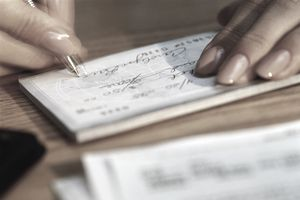 Woman signing check for bill, close-up