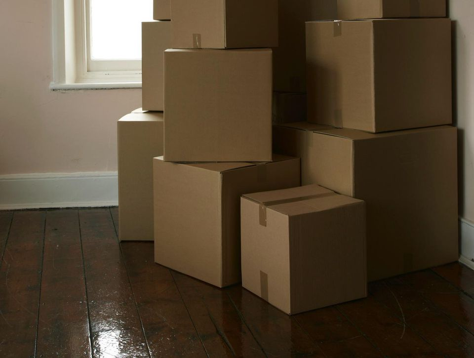 Packing boxes stacked in corner of room