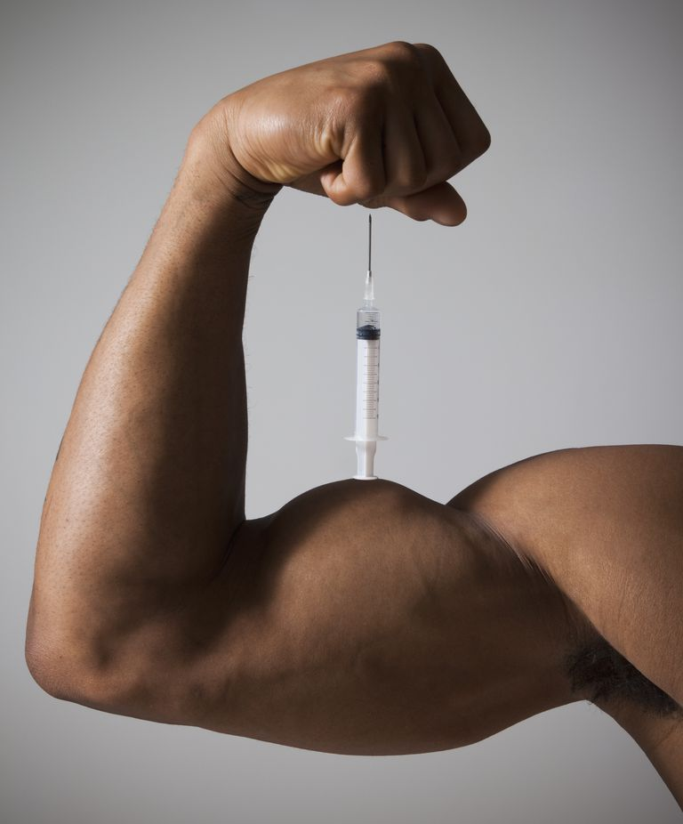 Syringe perched on a flexed muscular arm