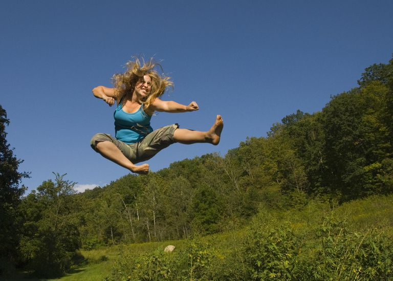 Young woman doing kung-fu moves in mid air
