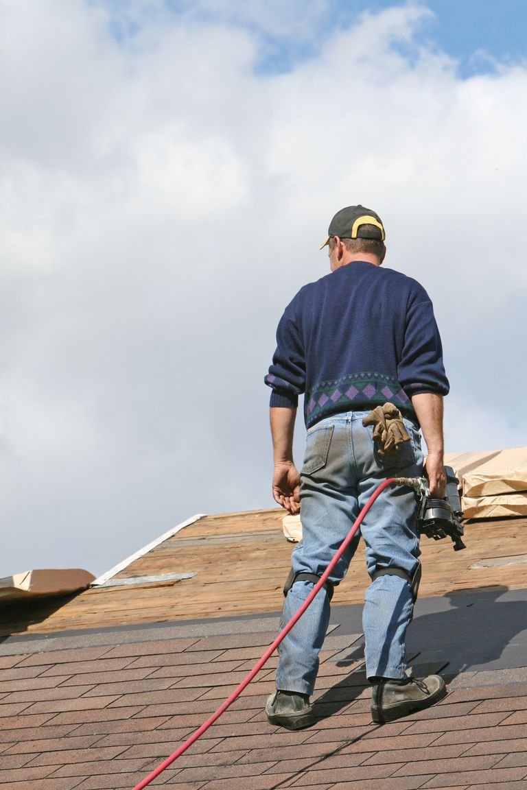 Roofer looking at shingles while holding a power tool
