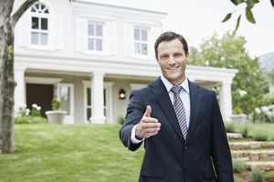 a man in a suit extending his hand in front of a house