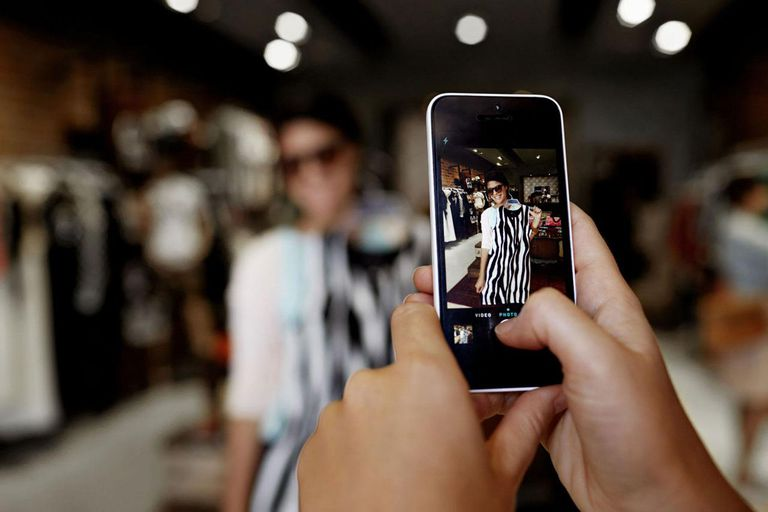 Close-up of hands taking picture of girlfriend trying on dress in shop