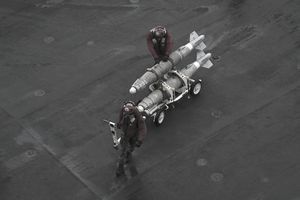 Gulf of Oman, June 13, 2013 - Marines move ordnance on the flight deck of the aircraft carrier USS Nimitz.