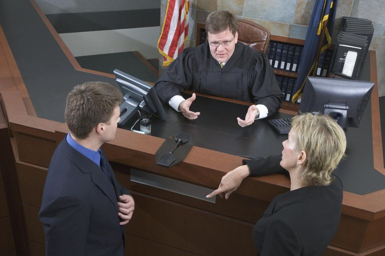 Lawyers talk with a judge.