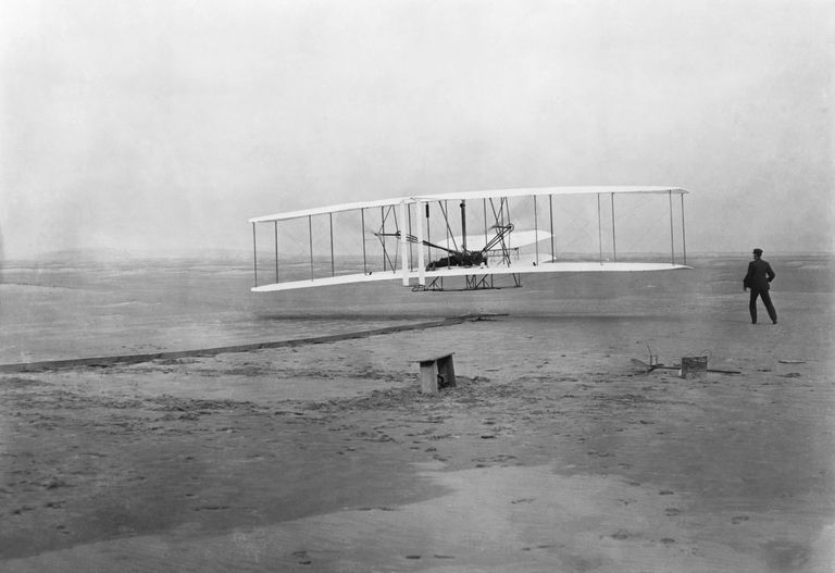 The Flyer takes off from Kill Devil Hill, with Orville Wright at the controls, while his brother Wilbur looks on, on December 17, 1903.