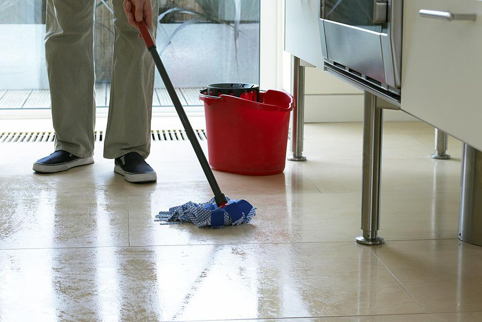 Man Cleaning a Kitchen Floor With a Mop and Bucket