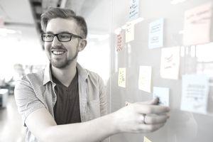 Smiling businessman arranging adhesive notes on whiteboard