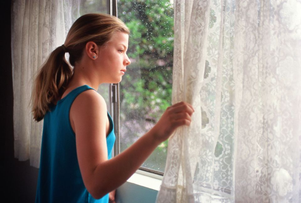 A picture of a young girl looking out the window