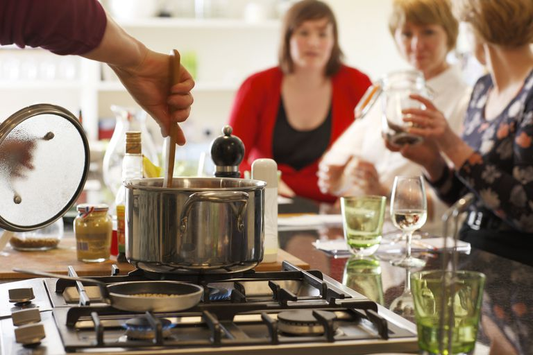 Stirring a pot on a stove in a kitchen island allows interaction with dinner guests