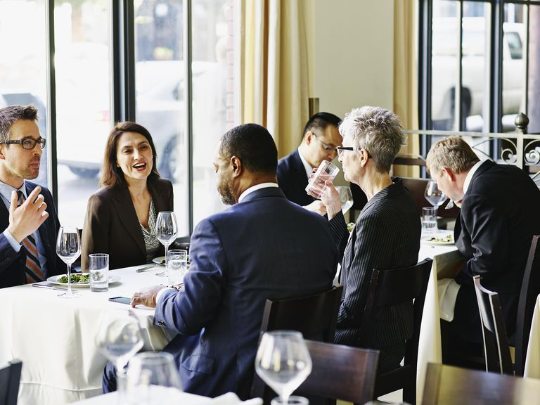 Group of business executives eating in restaurant