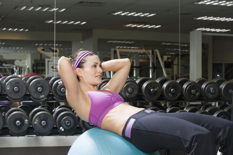 Mid adult woman doing sit-ups in gym weight room