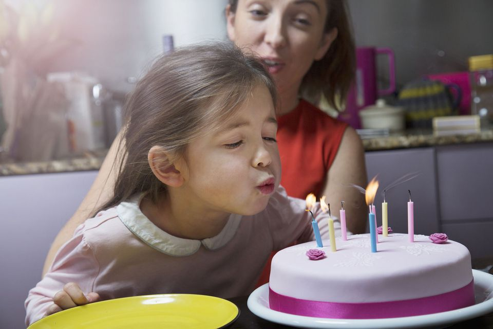 A picture of a child blowing out candles on a cake