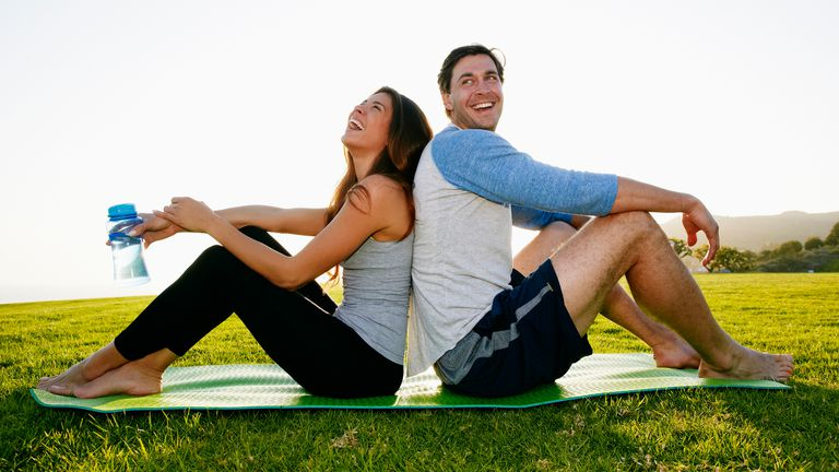 Man and woman sitting on a yoga mat laughing