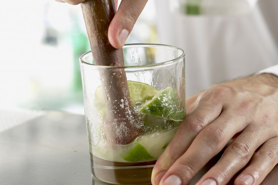 Muddling a lime wedges for making a Mojito cocktail.