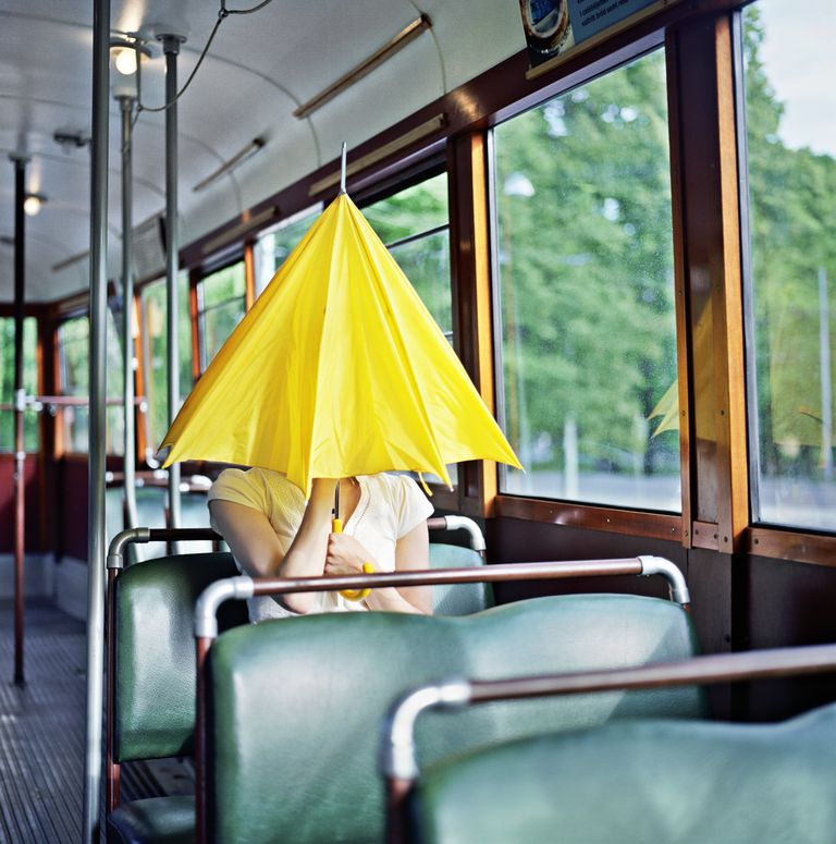 Woman hiding inside her umbrella on a bus.