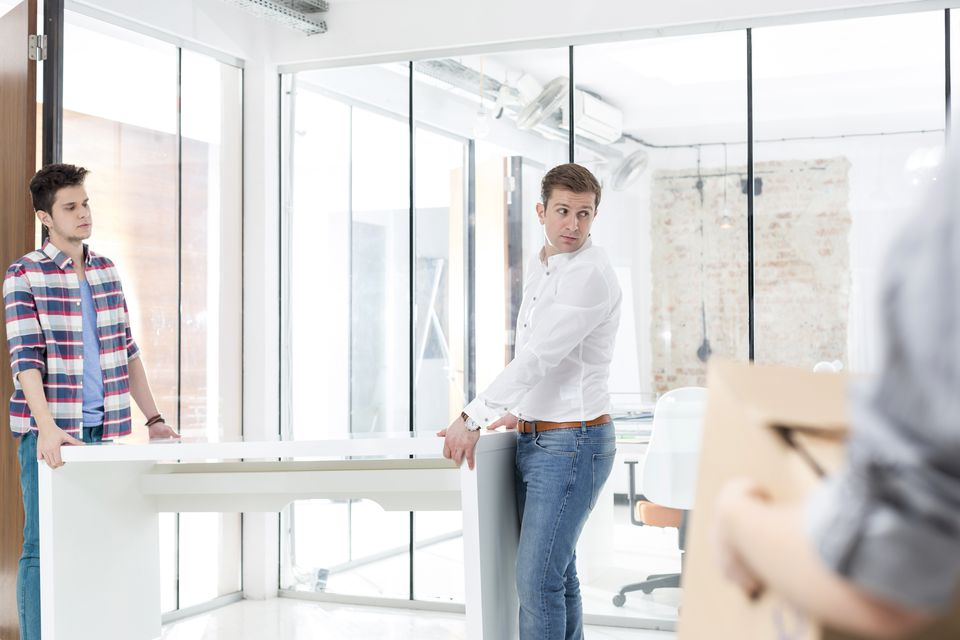 Colleagues carrying desk in new office