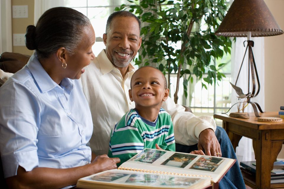 A picture of a child looking at a photo album with his grandparents