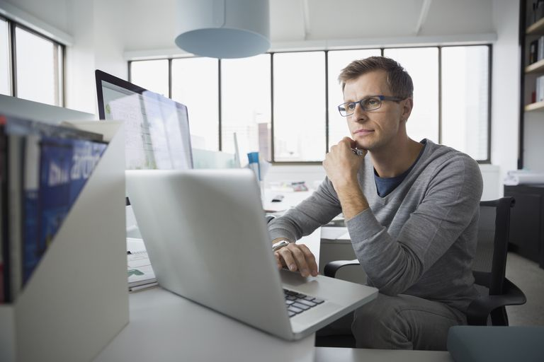 man using laptop in office with other computers