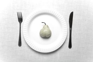 A single pear on a plate, representing control.