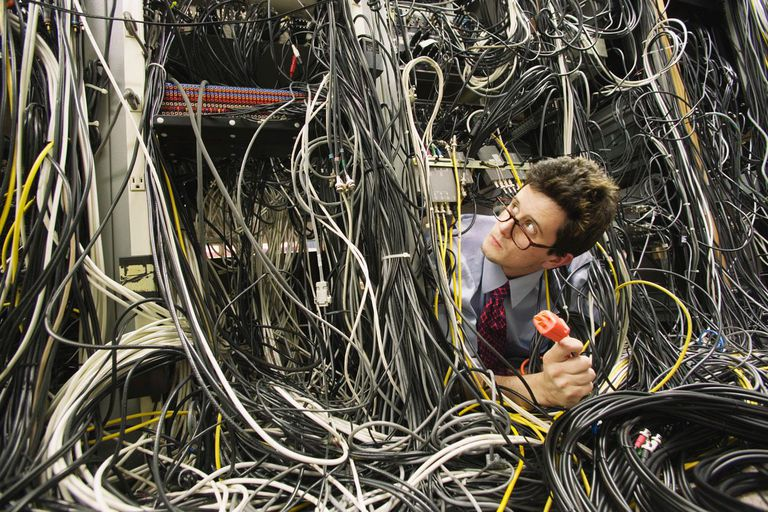 Young computer worker buried in network cables, holding plug