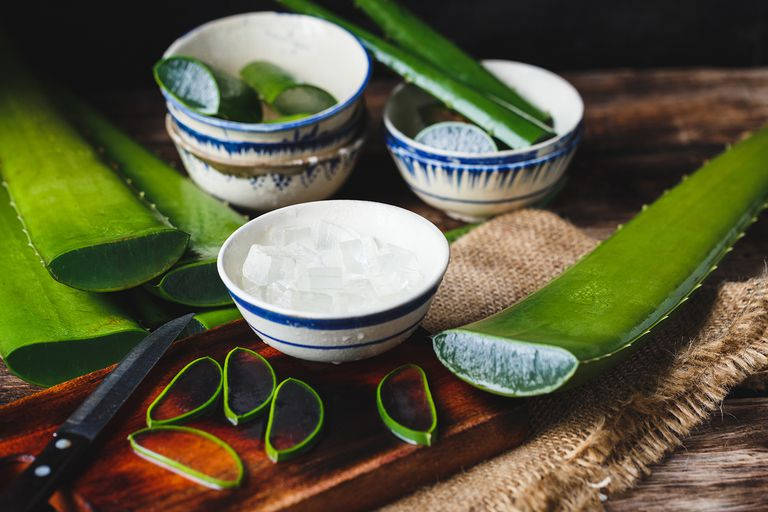Close-Up Of Aloe Vera Slices With Bowls On Cutting Board.