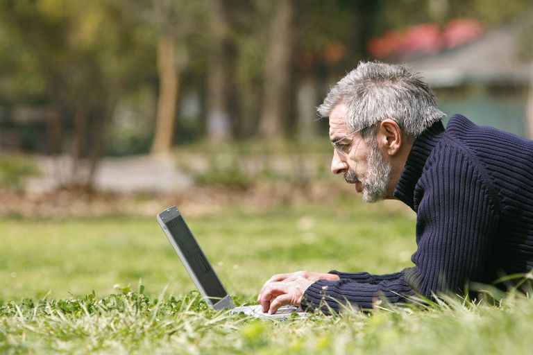 Man lying on the grass using laptop