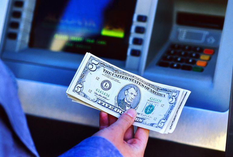 Person holding money withdrawn from on an automatic cash machine