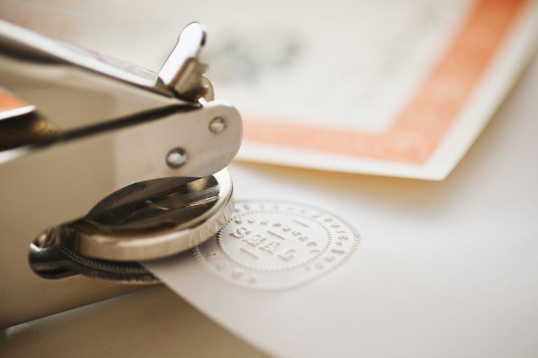 Close up of stamper making seal on paper