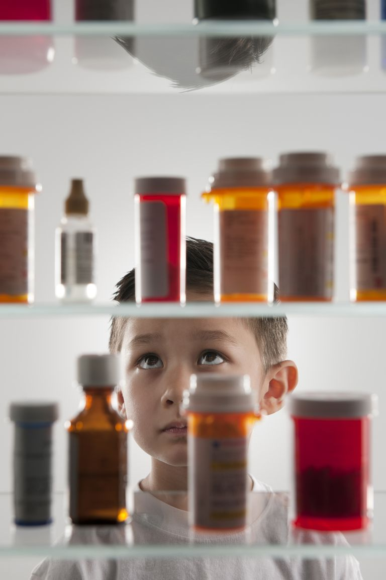 Child looking at medicine cabinet full of perscription medication