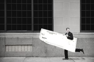 a businessman running down sidewalk carrying a life-sized check