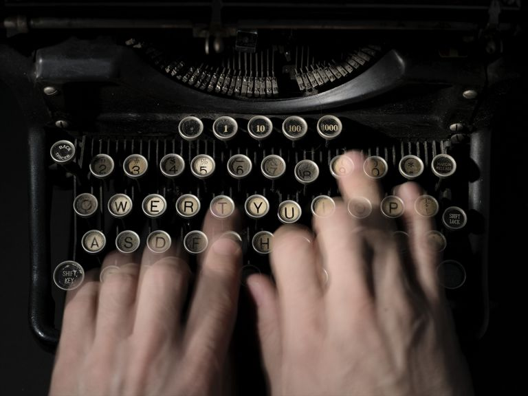 Close-up of fingers on a typewriter