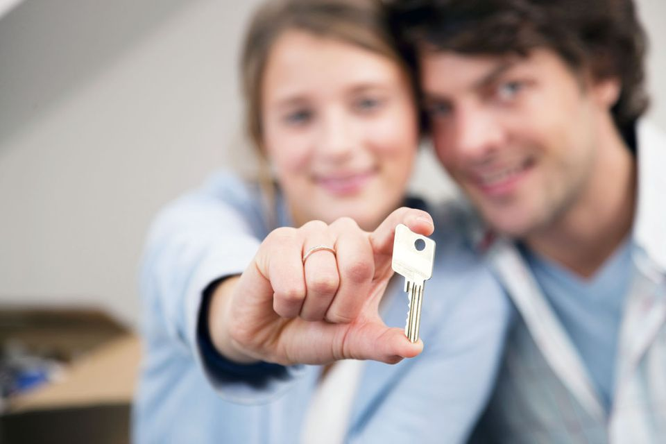 Couple holding a key to their new home.