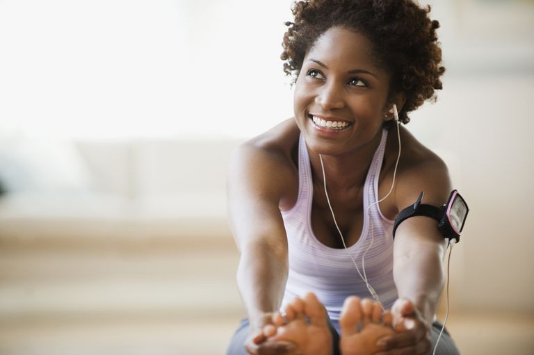 Black woman stretching and listening to mp3 player